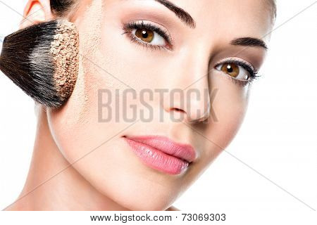 woman  applying dry cosmetic tonal foundation  on the face using makeup brush.