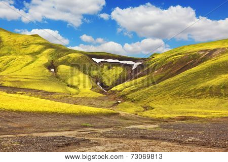 Green moss on smooth slopes and white spots snowfields in the gullies. Magnificent colorful mountains. Reserve Landmannalaugar, Iceland