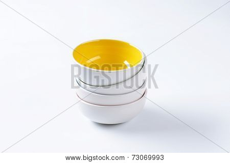 four stacked deep bowls, with yellow one on the top