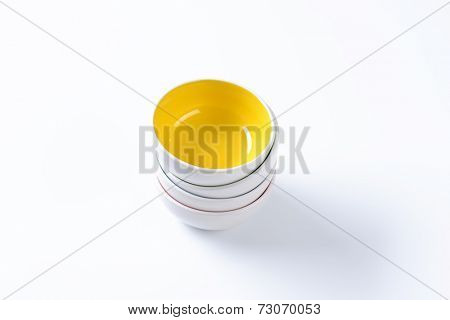 four stacked ceramic bowls with yellow one on top