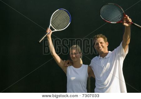 Tennis Partners Standing Side By Side, Arms Around, Raising Rackets In Victory