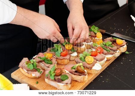 Chef is making bruschettas with beefsteak and pesto sauce
