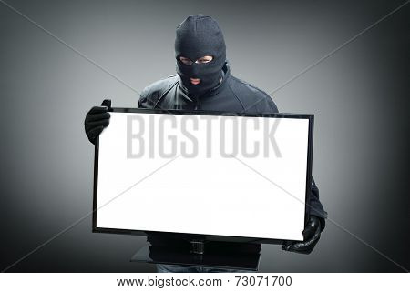 Thief stealing computer monitor or television concept for hacker, security or insurance with space on screen for message
