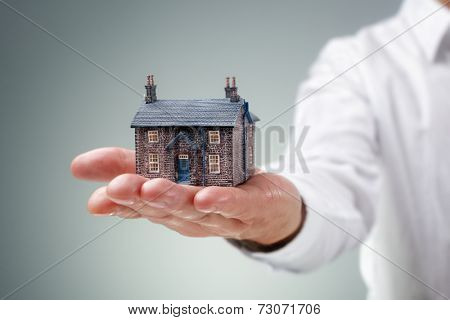 Man holding miniature model house concept for home, real estate, insurance or buying and selling property
