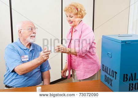 Volunteer gives an I Voted sticker to an elderly female voter.