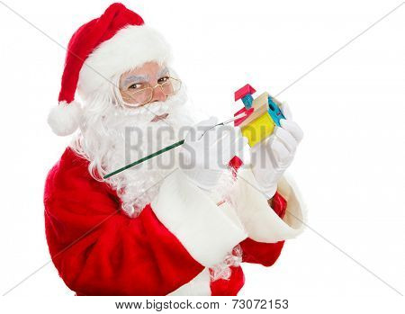 Santa painting a child's toy for Christmas.  Isolated on white.