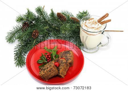 Christmas fruitcake and eggnog on white background.