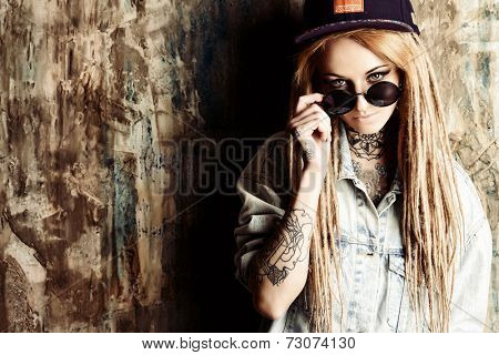 Modern teenage girl with blonde dreadlocks over grunge background. Jeans style. Modern generation.