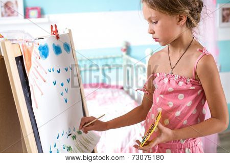 7-8 years old child drawing on easel in child room at home