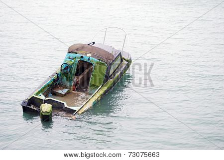 Lonely half sunk abandoned boat in middle of river
