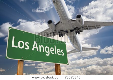 Los Angeles Green Road Sign and Airplane Above with Dramatic Blue Sky and Clouds.