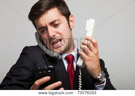 Stressed businessman talking on many phones at once