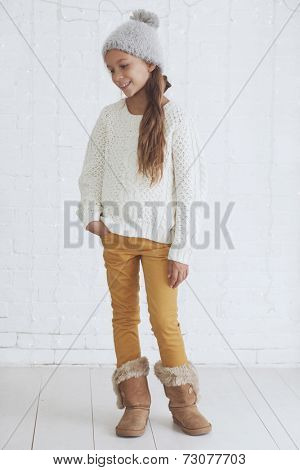 Cute teenage girl 8-9 years old wearing knit trendy winter clothes posing over white brick wall