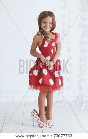 5 years old kid girl wearing stylish retro dress and heels posing over white background