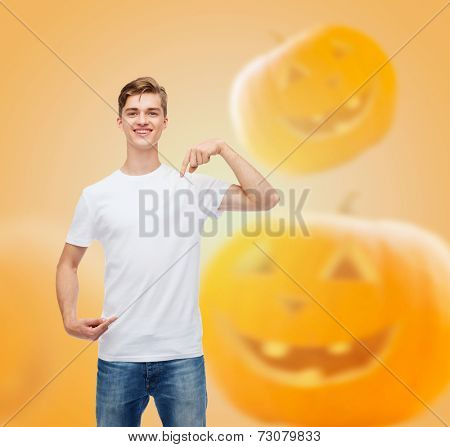 holidays, advertisement and people concept - smiling young man in blank white t-shirt pointing fingers at himself over halloween pumpkins background