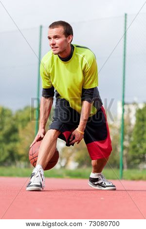 Young man on basketball court dribbling with ball. Streetball, training, activity. Real and authentic