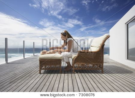Mother sitting in wicker sofa Playing with Son on ottoman on wooden porch side view