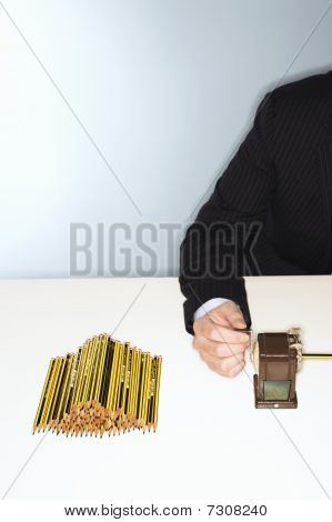 Businessman Sharpening Pencils At Desk, Mid Section