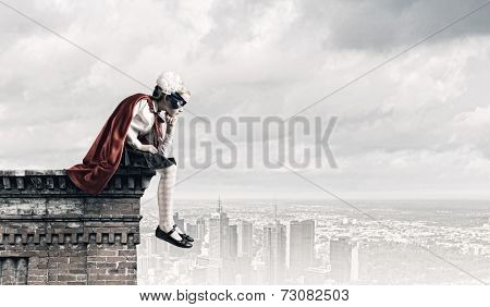 Cute supergirl of school age sitting on top of building