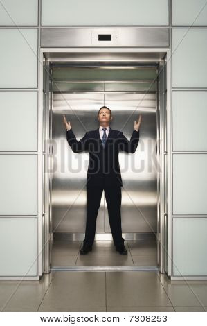 Businessman Arms Raised In Elevator, Front View