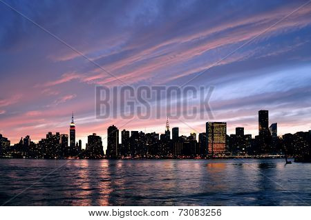 New York City Manhattan midtown silhouette panorama at sunset with skyscrapers and colorful sky over east river