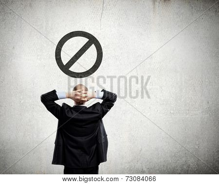 Rear view of thoughtful businessman looking at prohibition sign