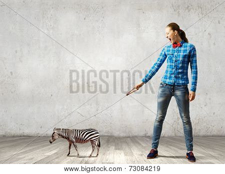 Young woman in casual holding zebra on lead