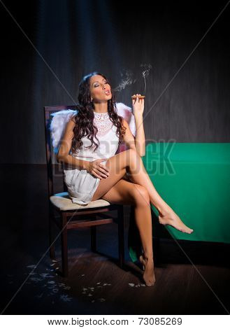 Smoking angel sits at the table