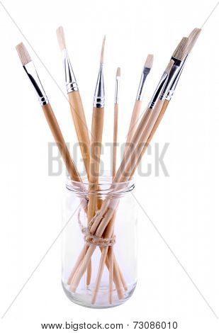 Paint brushes in glass jar isolated on white