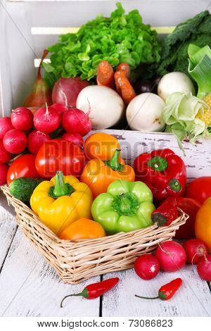 Vegetables in crate and in basket on white wooden box background