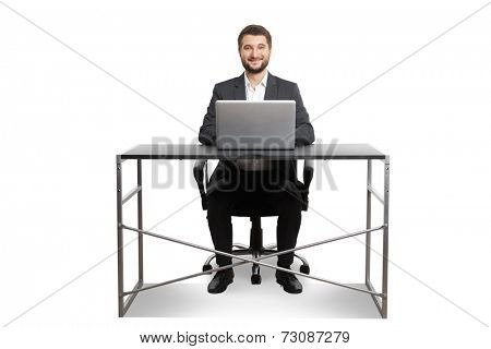 smiley successful businessman sitting at the table with laptop and looking at camera. isolated on white background