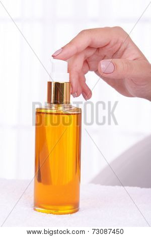 Woman hands holding body Oil close up