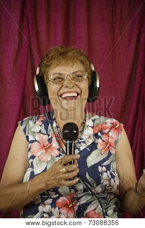 Woman wearing earphones and holding microphone