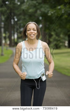 Portrait of woman jogging through park listening to music