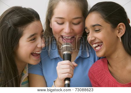 Three girls singing with microphone