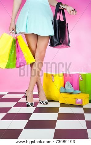 Fashion shopping concept, young trendy woman with shopping bags wearing high heels