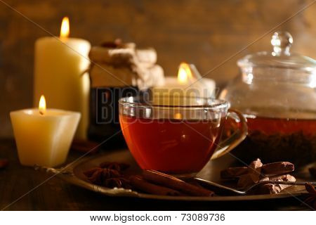 Composition with tea in cup and teapot and candles on table, on wooden background
