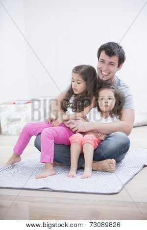 Smiling young man with daughters sitting in his lap at home