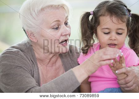 Senior woman helping granddaughter in counting fingers at home