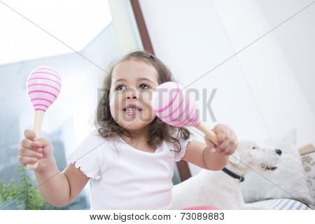 Cute girl playing with maracas while sitting beside dog at home