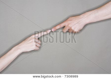 Man and woman almost touching extended index fingers close-up on arms