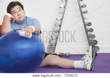 Wistful overweight Man sitting on floor with exercise ball in health club