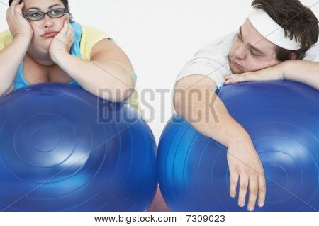 Disinterested overweight man and woman lying on Exercise Balls close up