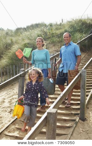 Family walking down wooden steps onto beach