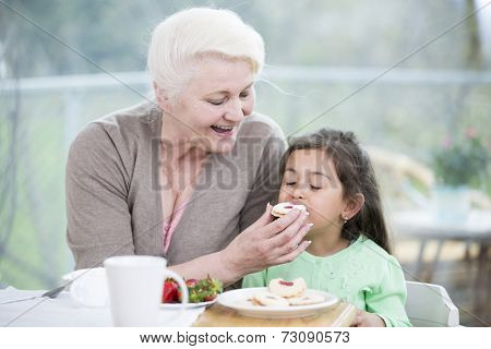 Happy senior woman feeding cookie to granddaughter at home