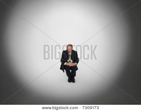 Businessman sitting under the spotlight