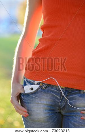 Smartphone with Headphones in Front Pocket of Woman Jeans