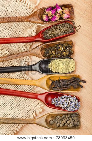 assortment of different dry tea in scoops on wooden table background, top view