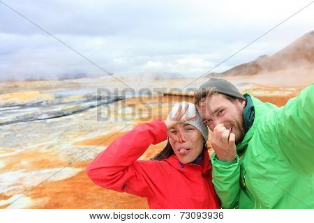 Iceland funny tourists couple having fun taking selfie photo with at landmark destination: Namafjall Hverarondor hverir mudpot also called mud pool hot spring or fumarole. Smell from sulfur on volcano