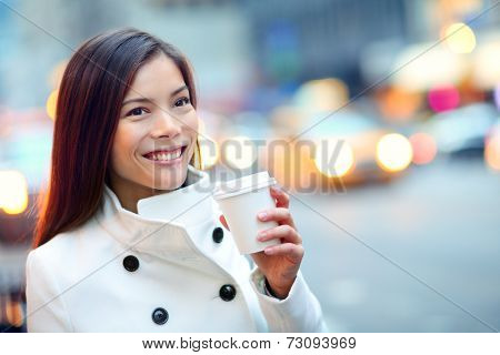 Young casual urban professional woman in New York City Manhattan drinking coffee walking in street wearing coat downtown with yellow taxi cabs in background. Female business woman.